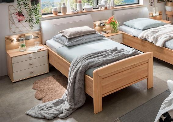 Zwei einzelne Seniorenbetten mit Tagesdecke und Kissen
