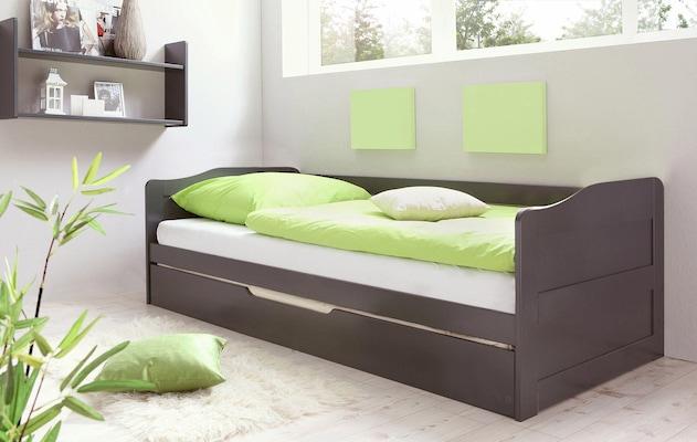 graues Kojenbett mit grüner Bettwäsche und Zierkissen